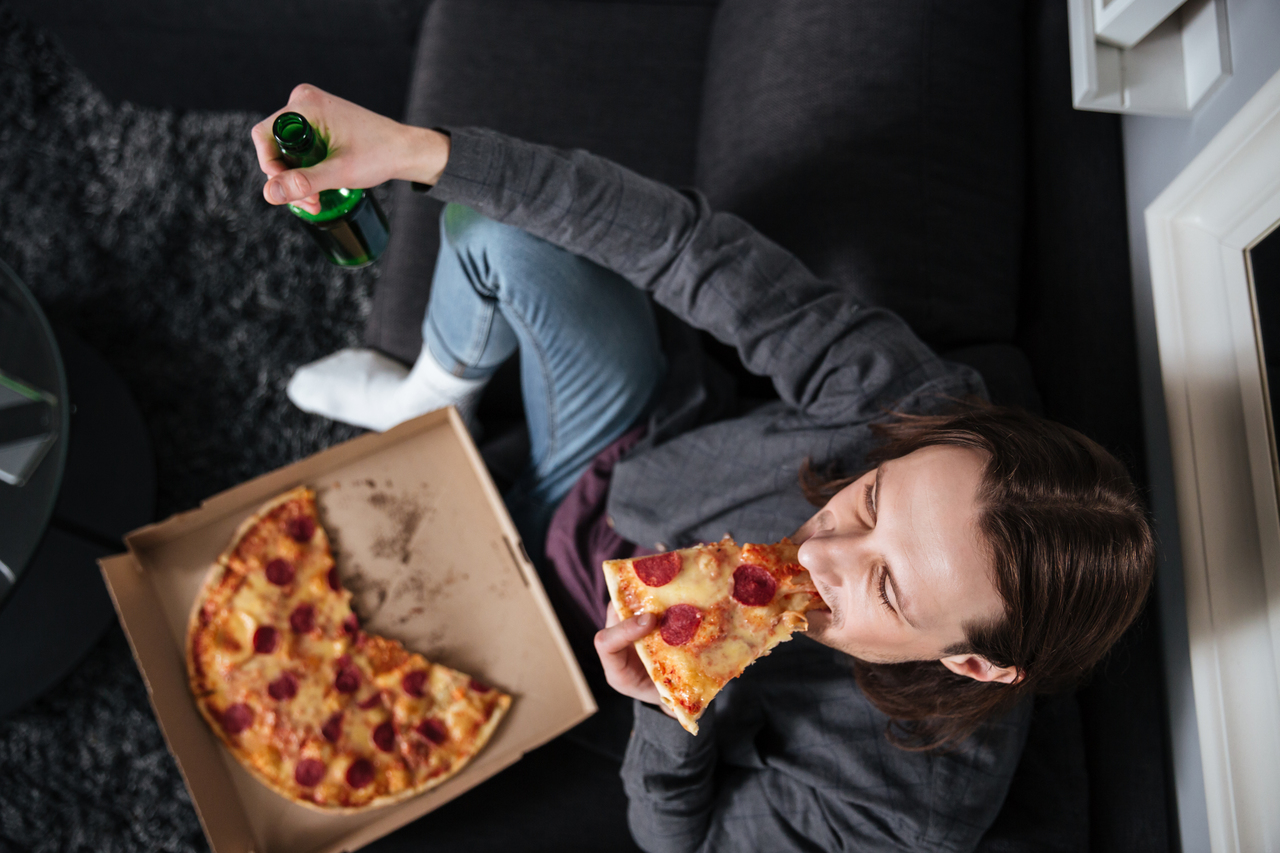 A man at home eating pizza