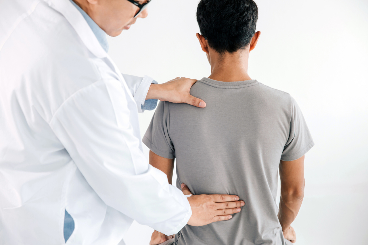 A chiropractor checking a patient