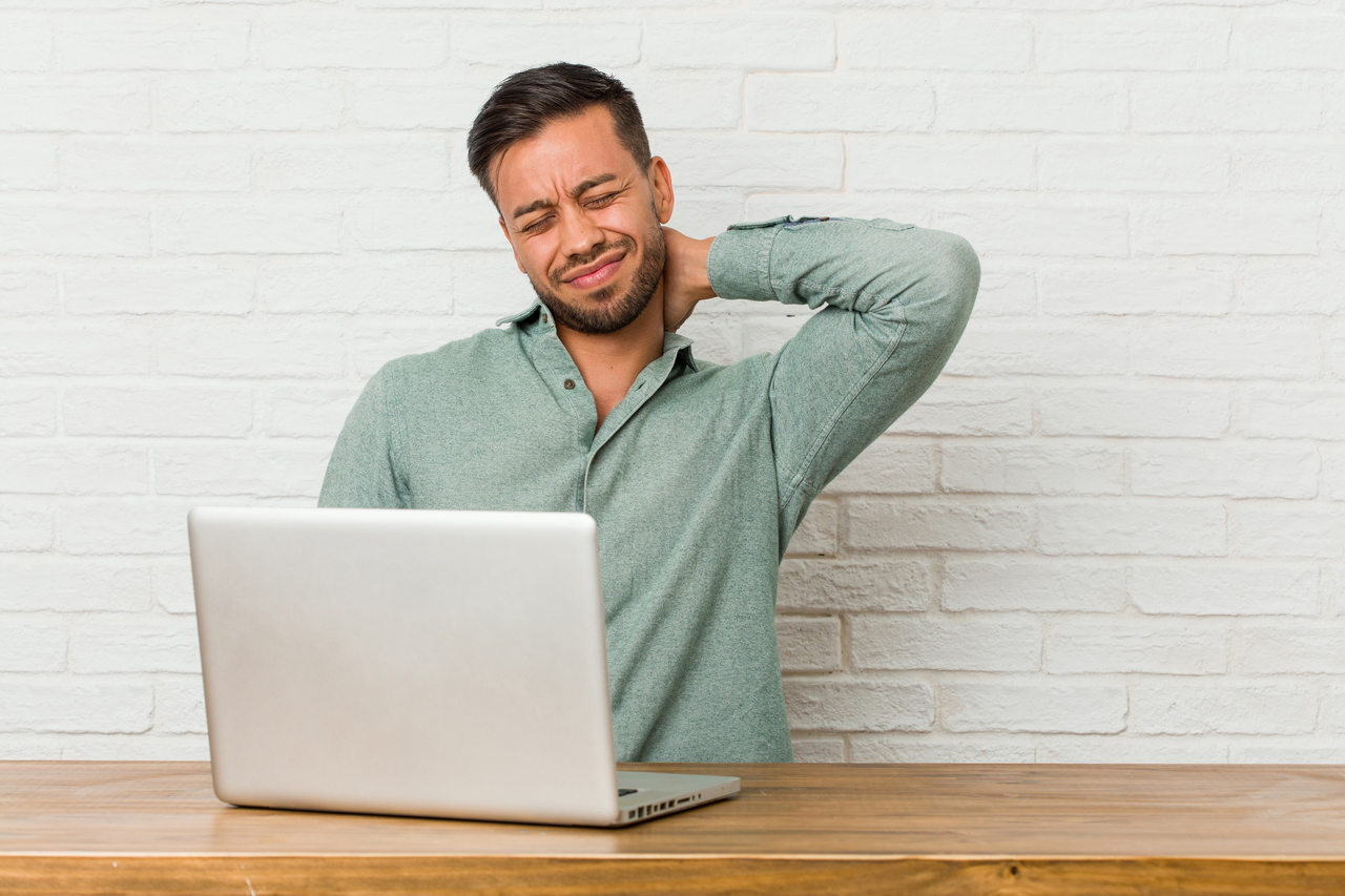 A young businessman with neck pain