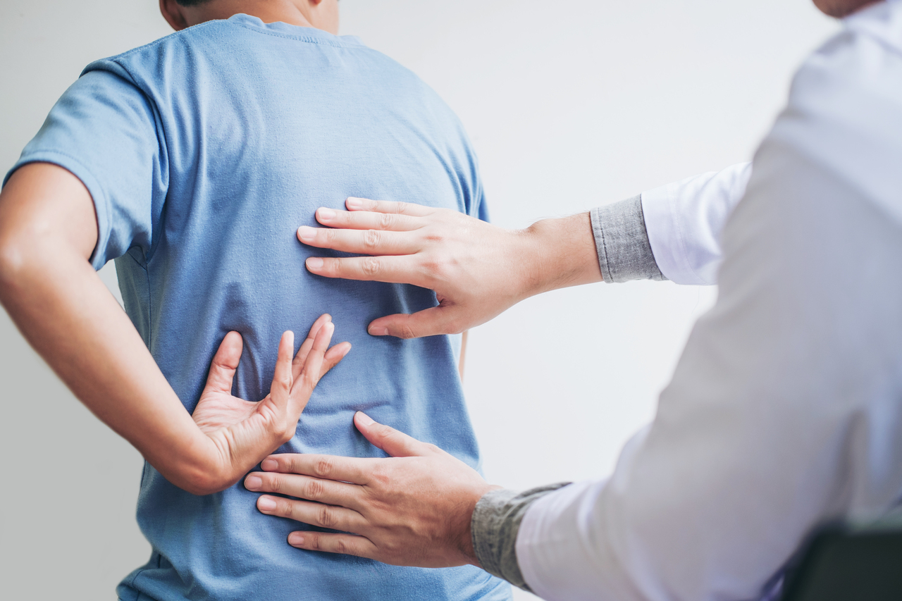 A man with back pain getting treated by a chiropractor