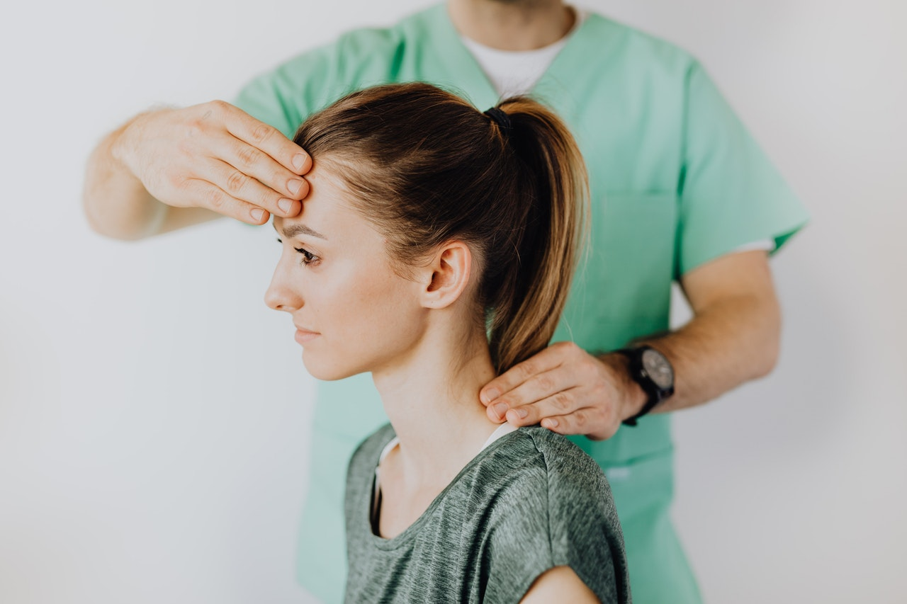 A woman receiving chiropractic treatment for neck pain