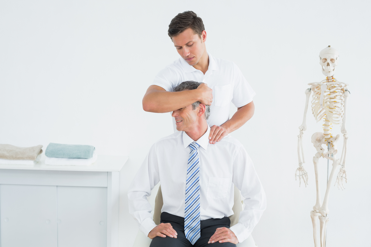 A chiropractor making an adjustment to a patient