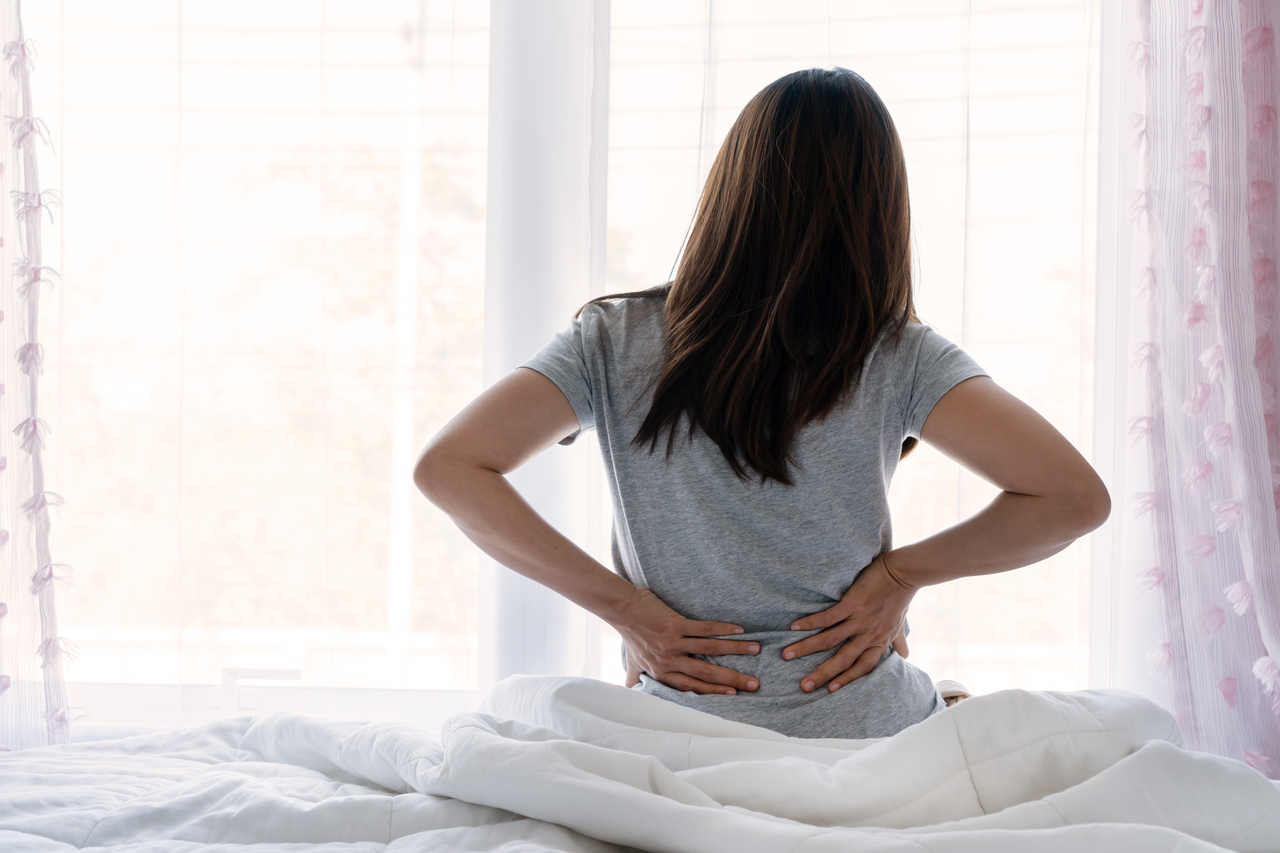 A woman with lower back pain due to bad posture