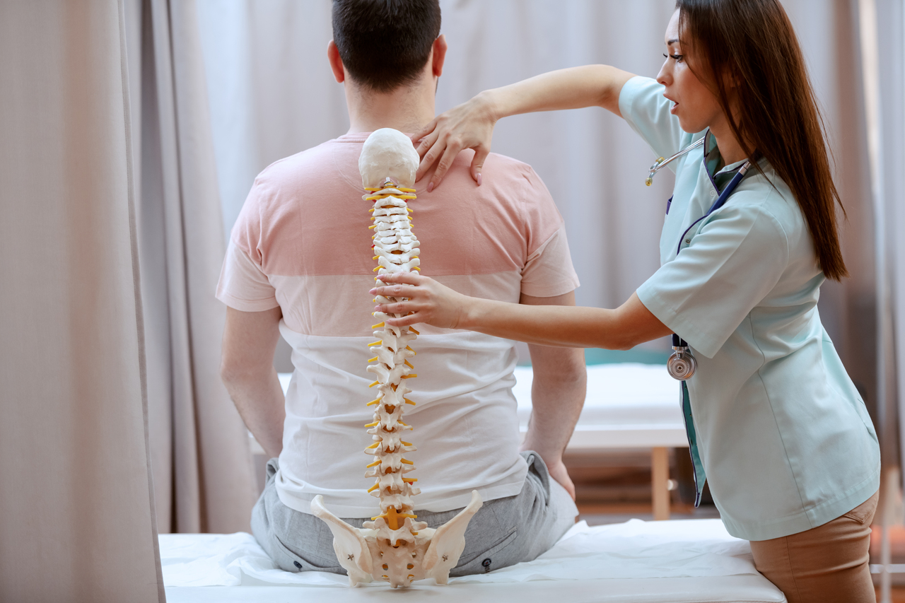 A woman checking a patient's spinal alignment