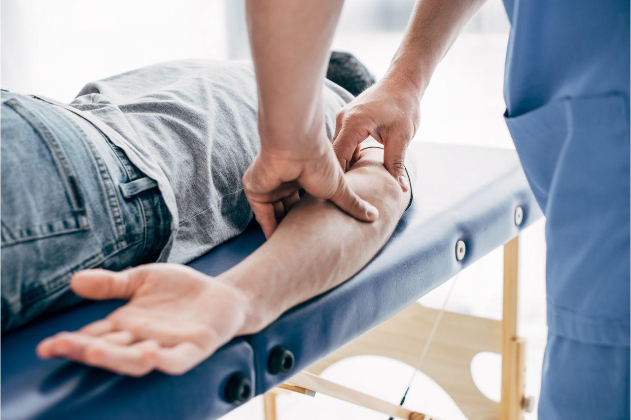 Chiropractor massaging a man's elbow