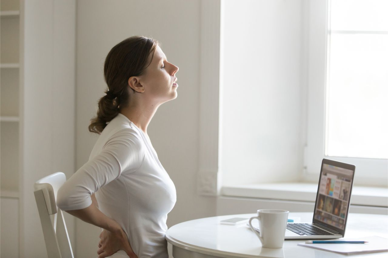 Woman with back pain while working