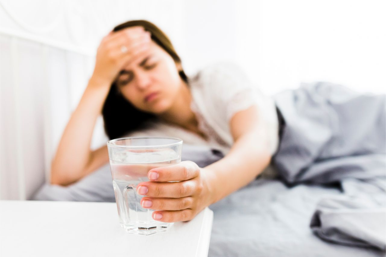 Woman with a headache about to drink water