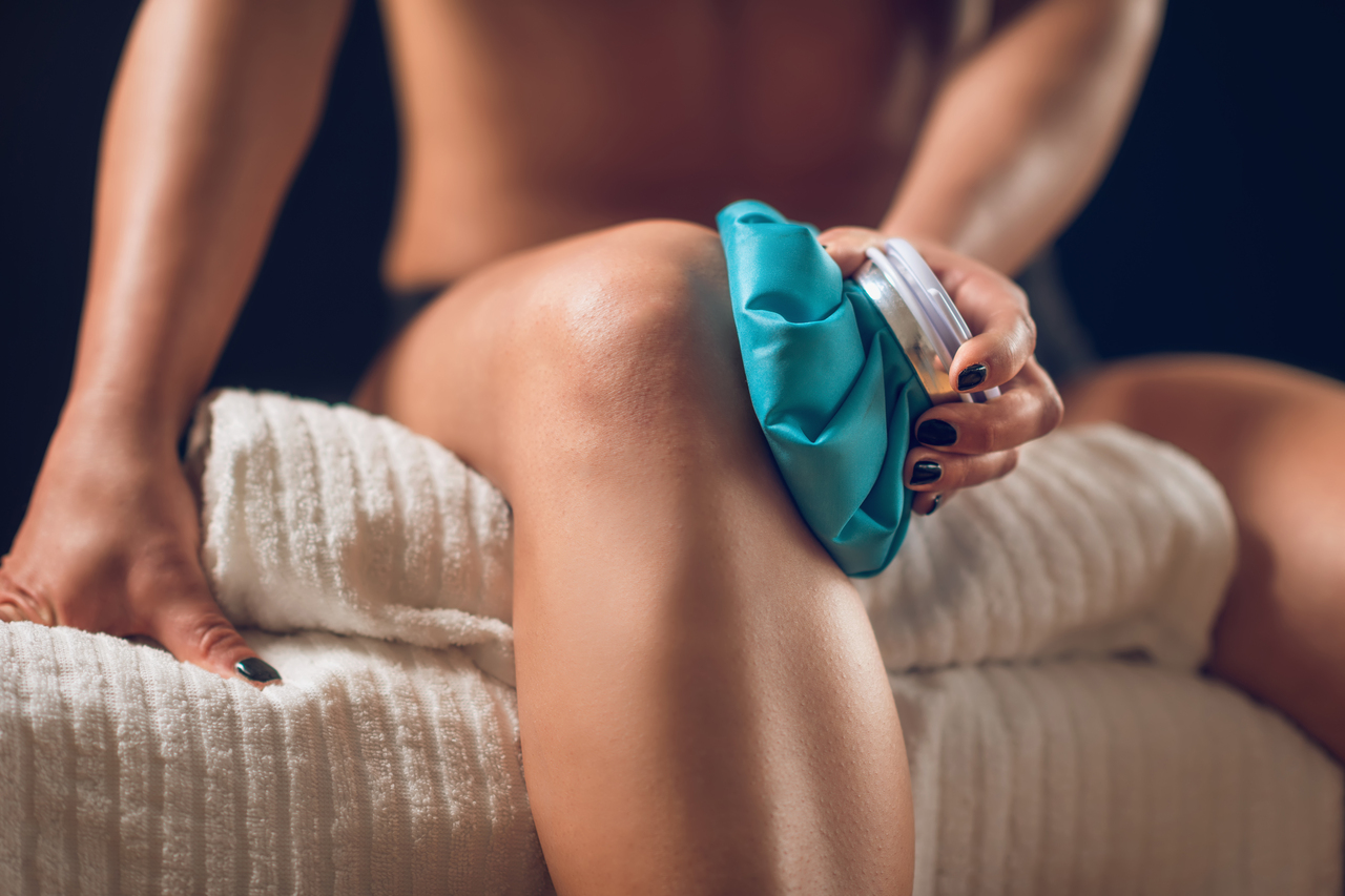Woman holding ice pack over knee