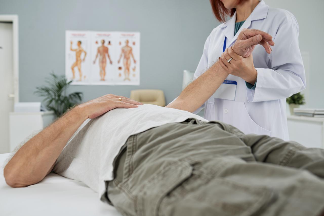 Chiropractor examining senior man
